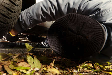 Assassin installing plastic explosive under car outdoor on parking place Stock Photo