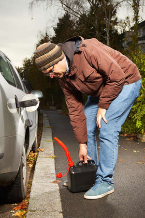Man with plastic canister filling car tank on street