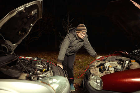 Man in evening winter time starting discharged car with other car and cables