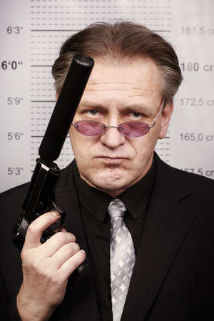 Bad criminal man portraited with silenced pistol in front of mug board Stock Photo