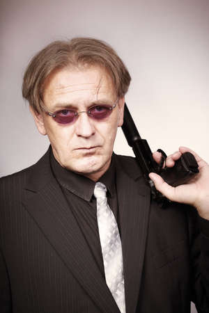 Ugly man armed with gun with silencer in style of mob criminal Stock Photo