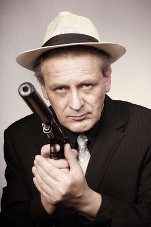 Older man armed with gun with silencer in style of mob criminal
