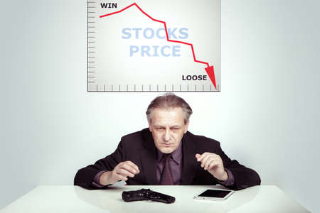 Man in suit is desperate about priceless stocks and planning end of his life by pistol Stock Photo