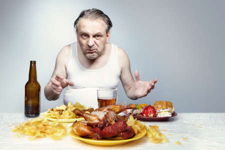 Aging man in a-shirt eating a lot of unhealthy food.