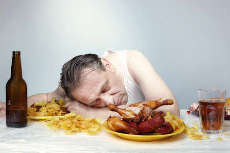 Aging man in a-shirt sleeping after eating a lot of junk food.