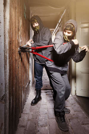 Two teenage burglars breaking in basement cellar with 30 inch bolt cutters