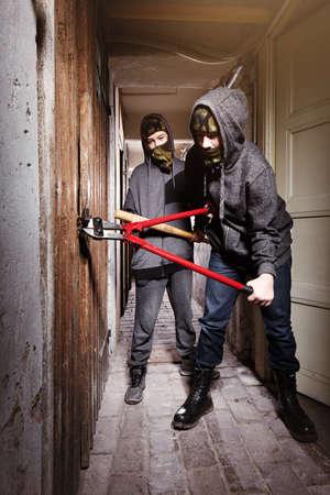 Two teenage burglars breaking in basement cellar with 30 inch bolt cutters