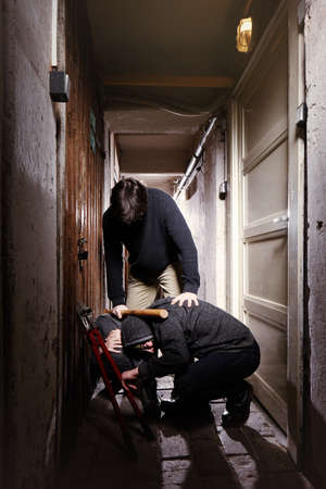 Two teenage burglars catched by adult man while breaking in basement cellar Stock Photo
