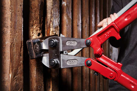 Red 30 inch bolt cutters in burglar teenager hands