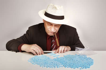Older dealer of drugs packing lots of pills Stock Photo