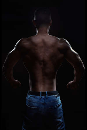 Muscular man posing his back in studio on black background