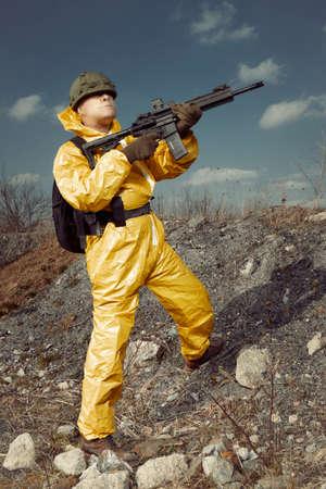 Freak gunman afraid of atomic war in yellow overall going noticeably through landscape