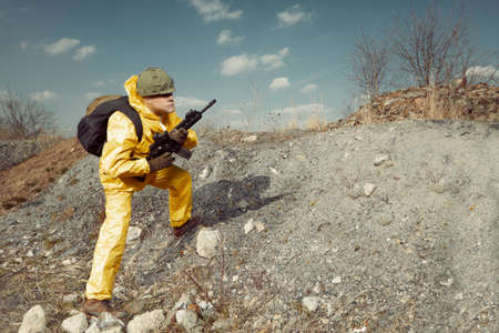 Freak gunman afraid of atomic war in yellow overall going noticeably through landscape