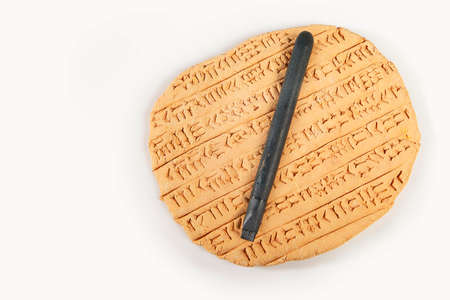 Ancient type of Akkad empire style cuneiform writing in brown clay with tool