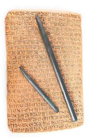 Ancient type of Akkad empire style cuneiform writing in brown clay with rest of dirty sand and writing tool