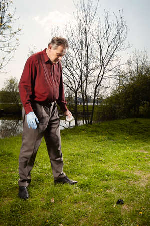 Man looking for falling meteorite made happy find on spring meadow Stock Photo