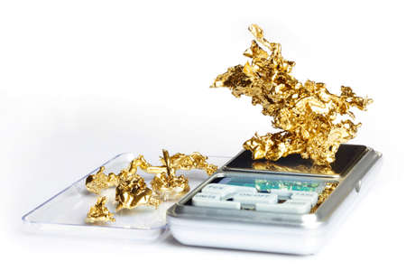Gold pieces and nuggets found by amateur prospector weighted on digital scale