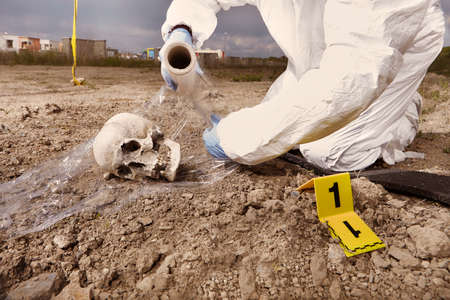 Police technician packing human skull found on plain construction yard during work