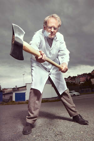 Older paramedic freak man in medical coat threating with double axe