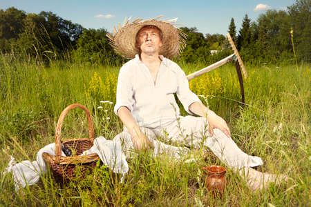 Village natural country man on summer meadow refreshing after mowing grass