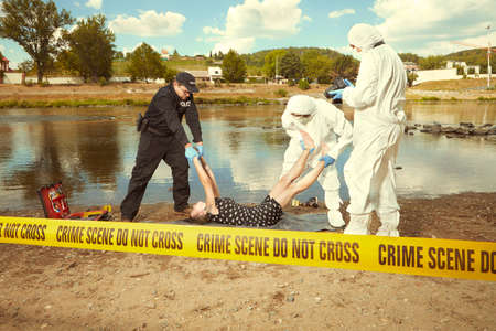Woman body in black apparel found drowned near summer river bank in city Standard-Bild - 105475358