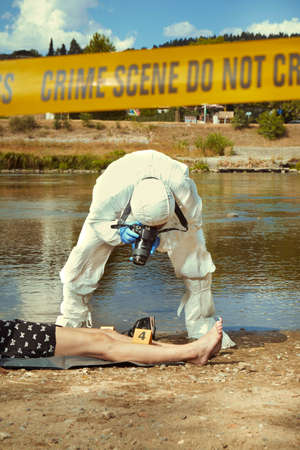 Woman body in black apparel found drowned near summer river bank in city Stock Photo