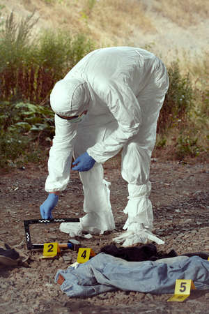 Criminologist technician in DNA free protective suit collecting evidences of probable criminal act Foto de archivo