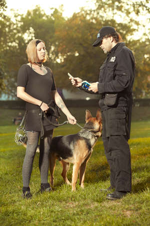 Policeman in uniform checking lady with german shepherd in city park Reklamní fotografie