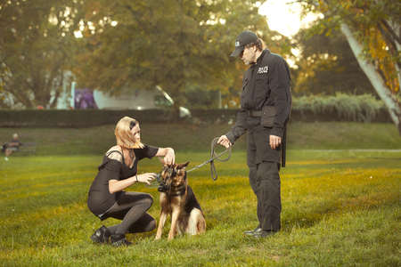 Policeman in uniform checking lady with german shepherd in city park Фото со стока