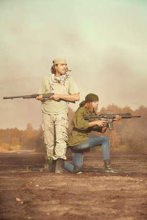 Guerilla, partisan or territory army couple watching around armed with guns Stock Photo