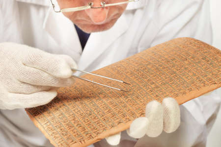Científico explorando el antiguo tipo de escritura cuneiforme de estilo Imperio Akkad en la mesa