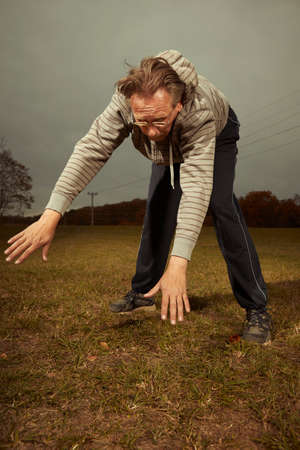 Aging older man exercising in sportsuit outdoor on meadow