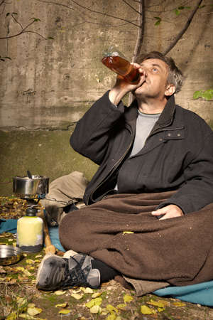 Ugly pauper man living outdoor drinking alcoholic beverages
