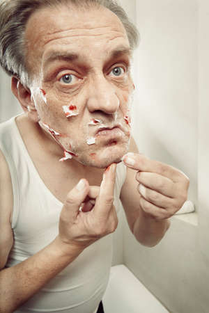 Aging man in a-shirt shaving face and cut himself with old style razor