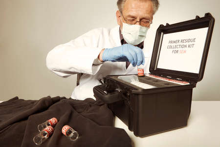 Proccess of collecting possible gunshot residue from suspected clothes in police lab Reklamní fotografie