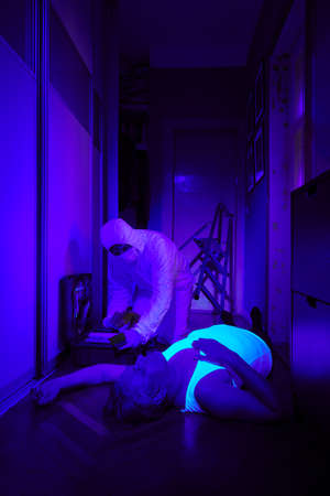 Checking place of unusual man death in ultra violet light Stock Photo