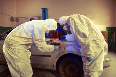 Crime investigation - developing of fingerprints on suspected car in police garage under UV light Reklamní fotografie