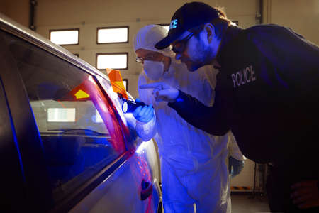 Crime investigation - police technician showing fingerprints to colleague on suspected car in garage with UV light