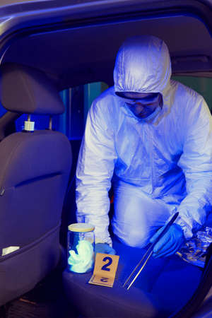 Crime investigation - collecting of odor traces in suspected car in police garage under UV light