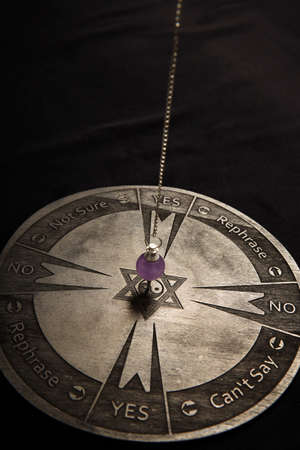 Properties of fortune telling - wooden spiritual chart and pendulum Stock fotó