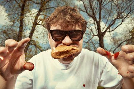 Man in street park eating hot dog with mustard, ketchup and dough bun
