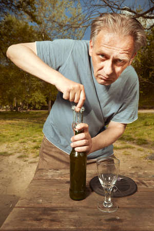 Older man in summer park drinking beer after spiritual connection with ghosts