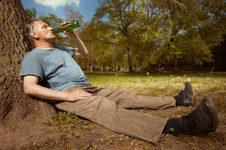 Older man in summer park drinking beer after spiritual connection with ghosts Stock Photo