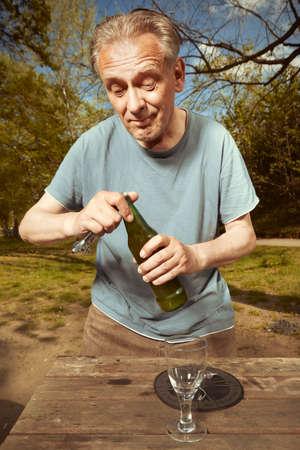 Older man in summer park drinking beer after spiritual connection with ghosts Reklamní fotografie