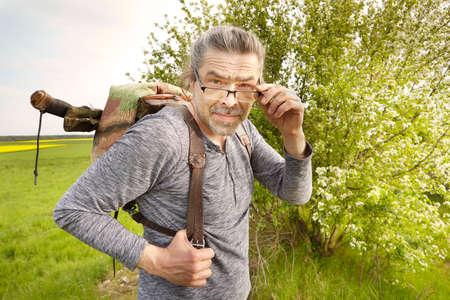 Mature man on trip in summer wilderness enjoying freedom
