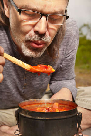 Mature man on trip in summer wilderness preparing food