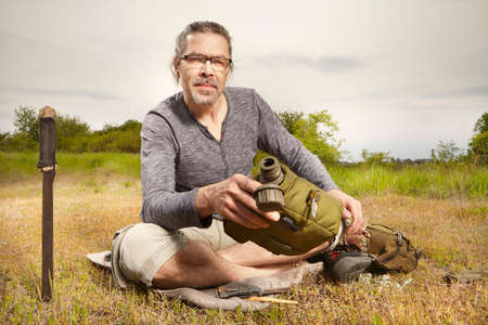 Mature man on trip in summer wilderness relaxing on meadow