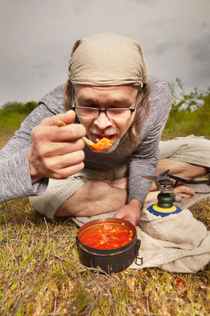 Mature man on trip in summer wilderness preparing food Reklamní fotografie