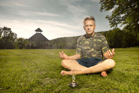 Older man practicing meditation rituals in summer city park Stock Photo