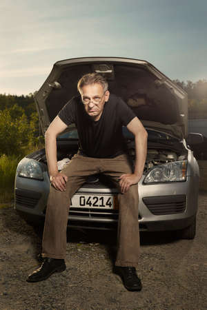 Aging desperate man trying to fix broken car engine on lonely way Stok Fotoğraf